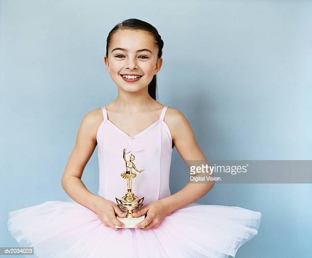 Portrait of a Young, Female Ballet Dancer Holding a Trophy