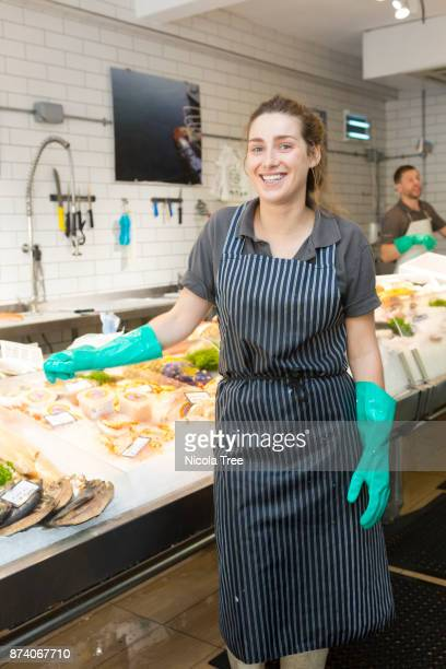 Portrait of a young Female Fishmonger standing in front of the display of fresh fish in a shop.
