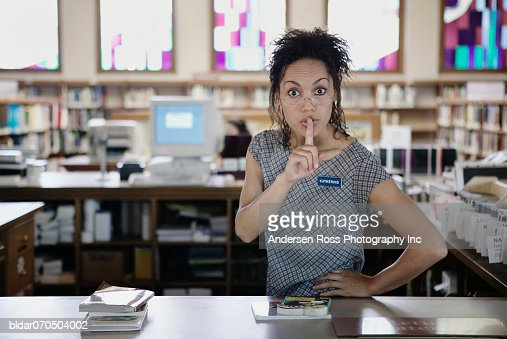 Portrait of a young female librarian standing in a library with a finger on her lips : Stockfoto