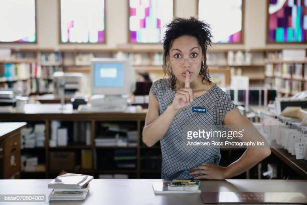 Portrait of a young female librarian standing in a library with a finger on her lips