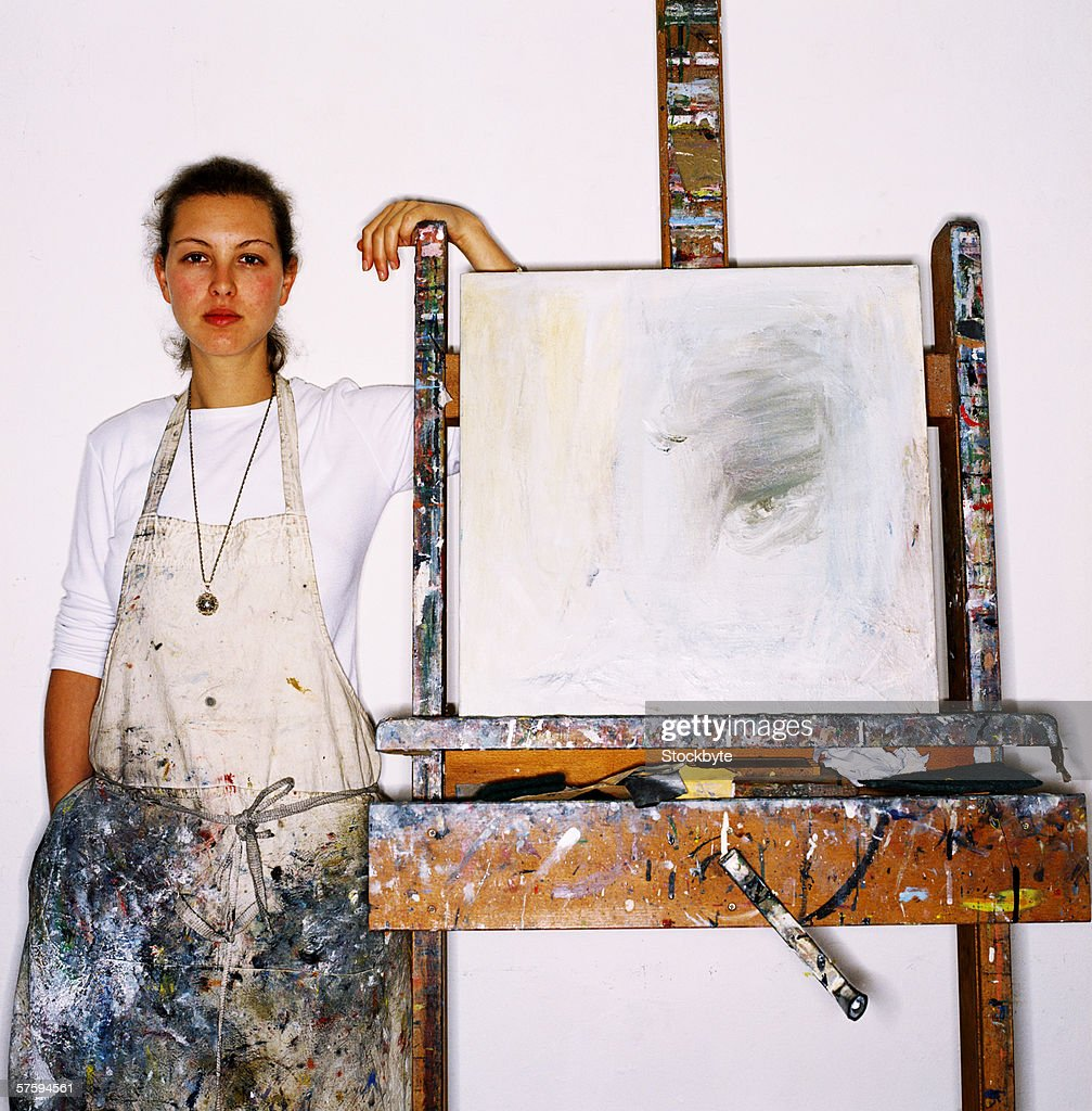 Portrait of a young female painter standing beside easel : Stock Photo