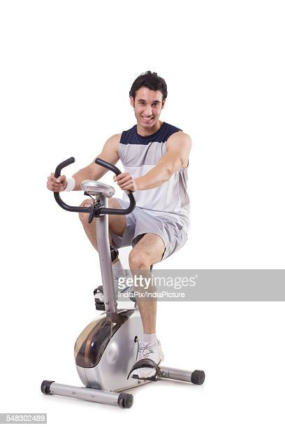Portrait of a young fit man on exercise bike over white background