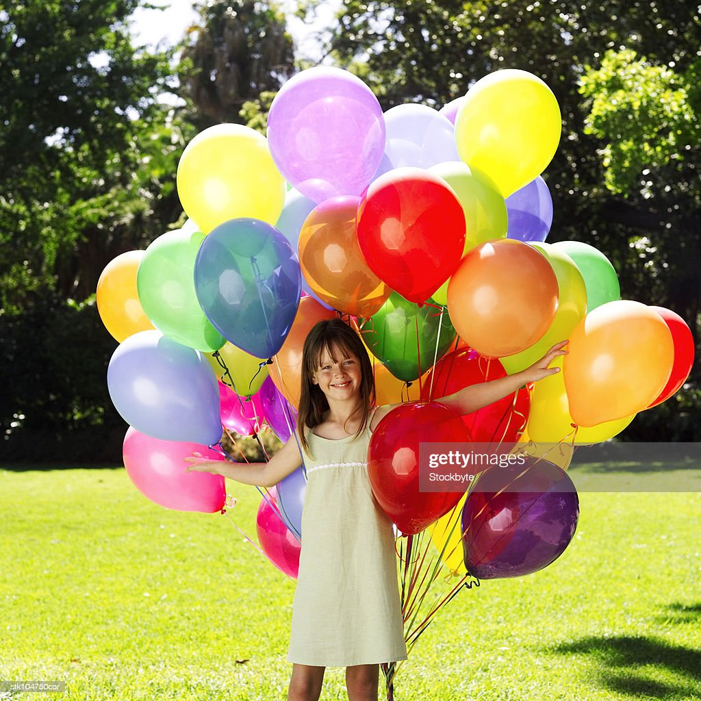 portrait of a young girl amongst colorful balloons : Stock Photo