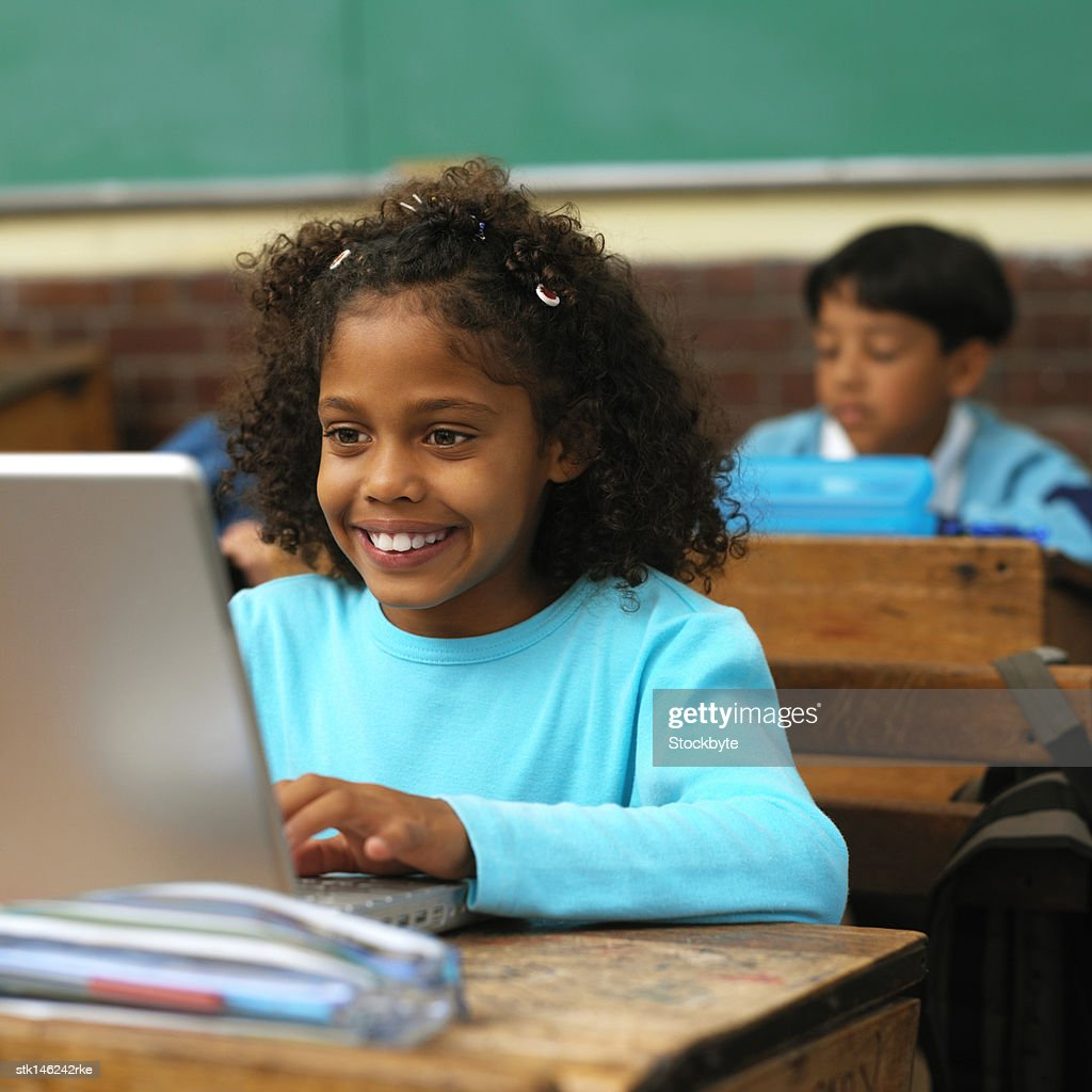 portrait of a young girl at school working on a laptop computer screen : Stock Photo