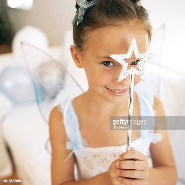 portrait of a young girl (4-6) dressed up in a fairy costume holding a wand in front for her face