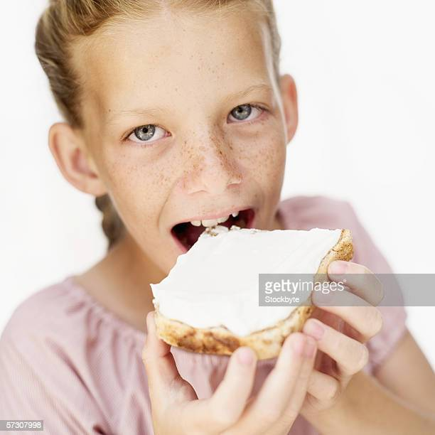 Portrait of a young girl (9-10) eating cheese on toast