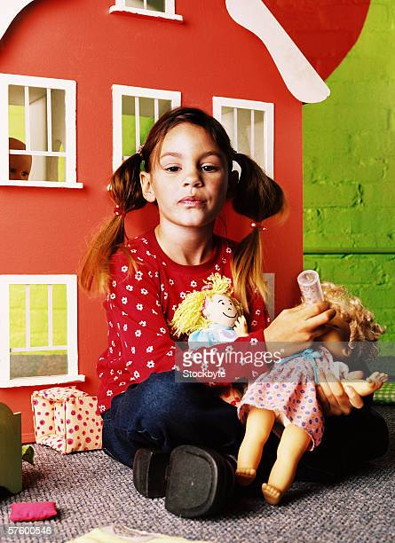 Portrait of a young girl (8-10) feeding her doll