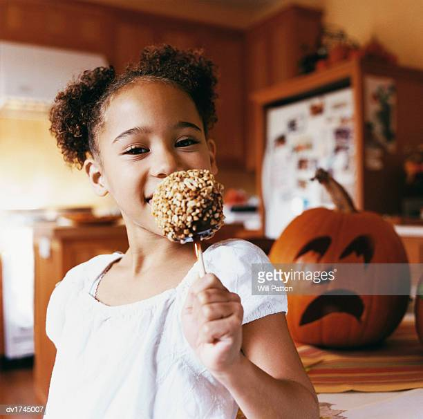 Portrait of a Young Girl Holding a Toffee Apple with a Jack O Lantern Behind Her