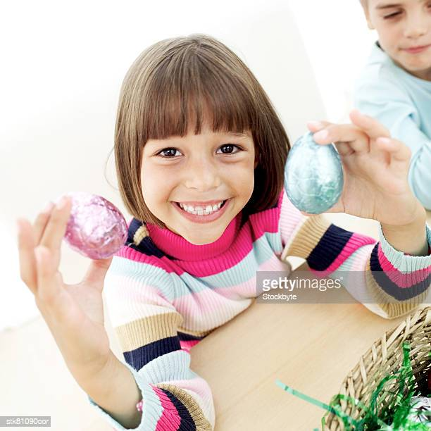 portrait of a young girl holding up two easter eggs