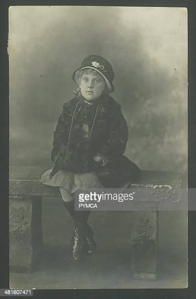 Portrait of a young girl in a coat and fur hand muff circa 1900s