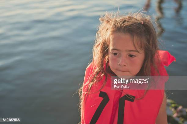 Portrait of a young girl in a safety vest fishing.