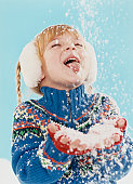Portrait of a Young Girl in Winter Clothing Sticking Out Her Tongue and Catching Snowflakes