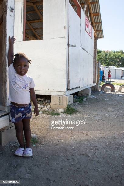 PortauPrince Haiti December 09 2012 Portrait of a young girl leaning at the entrance of a first aid barrack in the refugee camp Parc Colofe in...