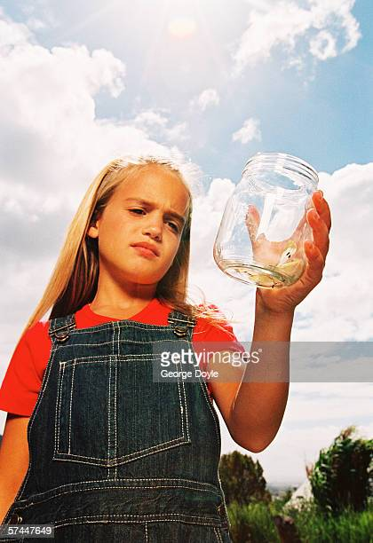 portrait of a young girl (8-12) looking at a jar