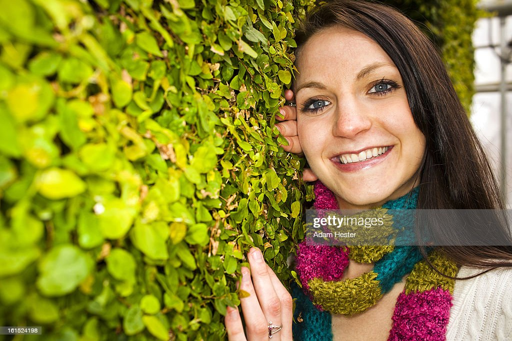 Portrait of a young girl near a wall with plants. : Stock Photo