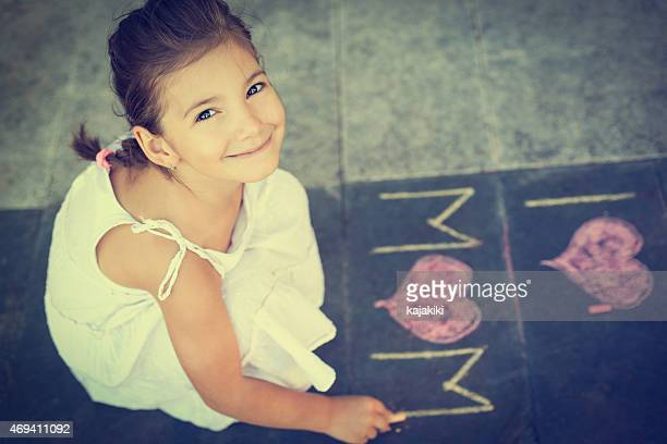 Portrait of a young girl playing with sidewalk chalk