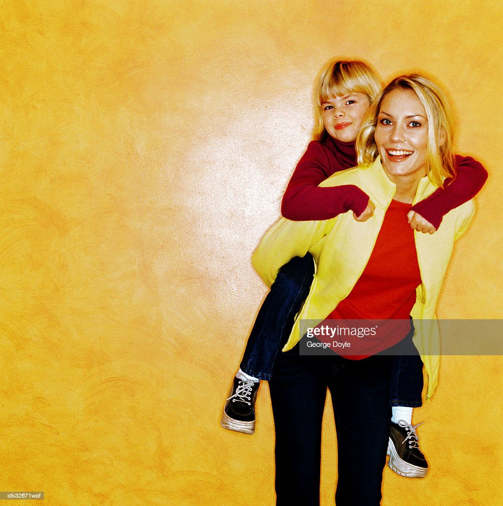 portrait of a young girl (4-6) riding piggyback on her mother : Stock Photo