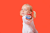 Portrait of a young girl showing vote badge over pink background