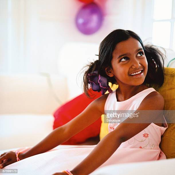 portrait of a young girl (4-6) sitting on a couch and smiling