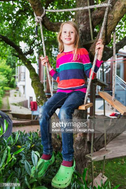 Portrait of a young girl sitting on a tree swing in her backyard