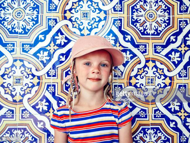 Portrait of a young girl standing against a wall covered in patterned tiles