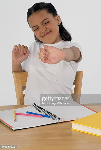 Portrait of a young girl stretching at her desk