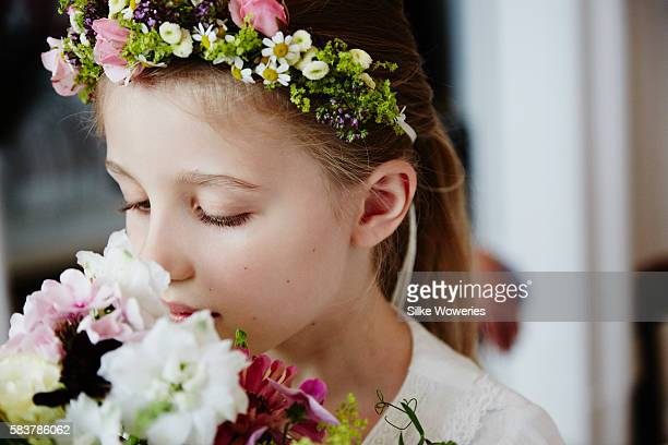 portrait of a young girl take a smell at a bouquet of flowers
