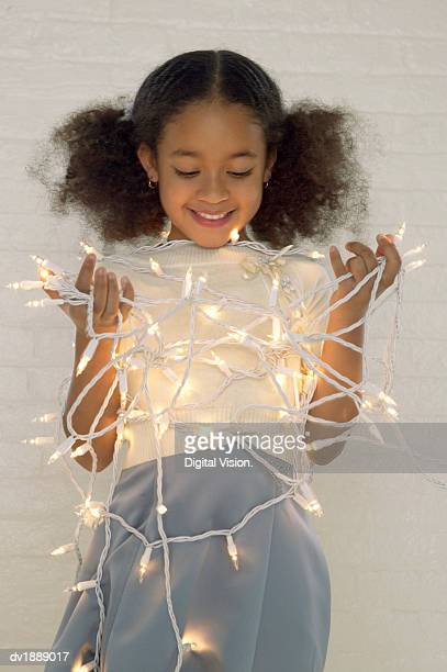 Portrait of a Young Girl Tangled Up in Christmas Lights