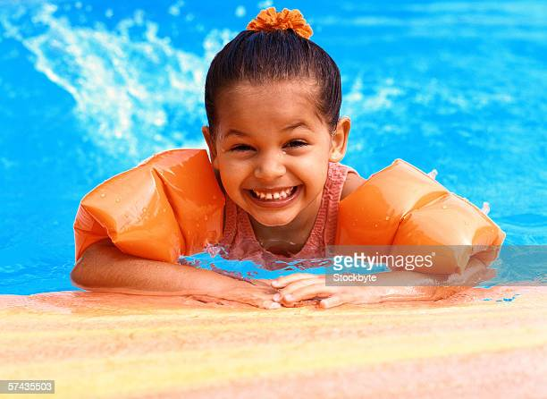 portrait of a young girl (3-5) wearing arm floats in a swimming pool