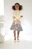Portrait of a Young Girl Wrapped in Christmas Lights