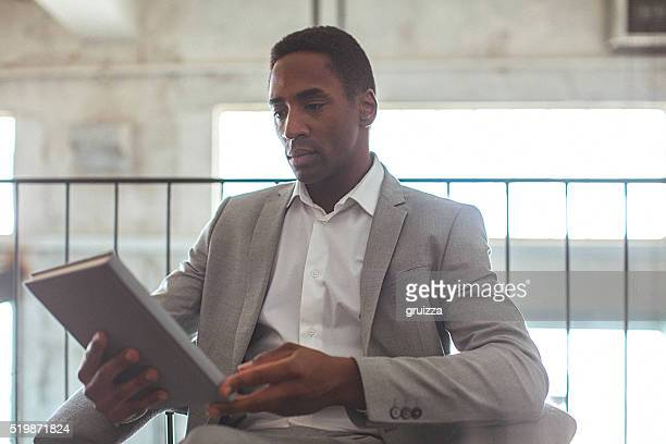 Portrait of a young handsome businessman holding agenda