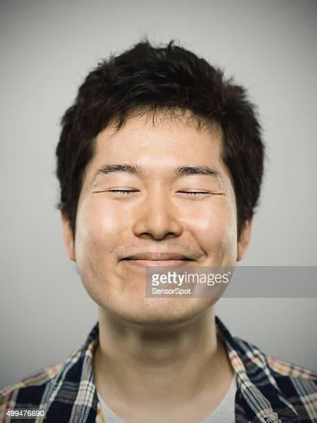 Portrait d'un jeune homme heureux en regardant caméra japonais