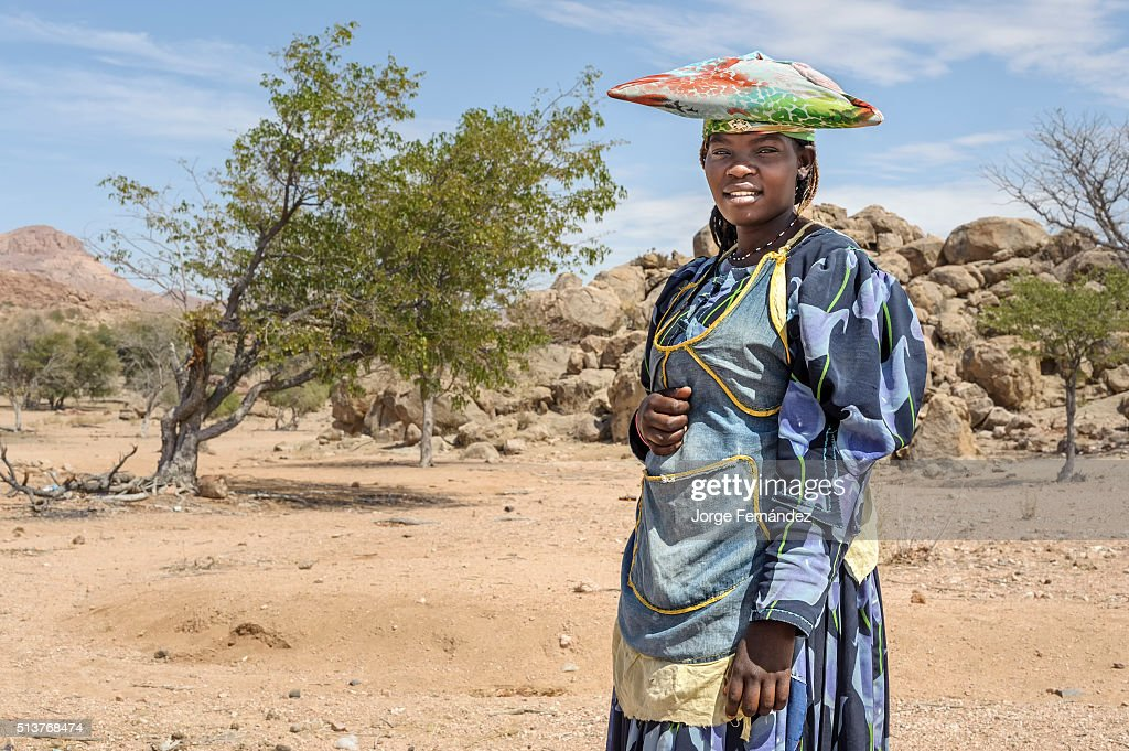 Portrait of a young Herero woman with traditional dress and hat outside her village