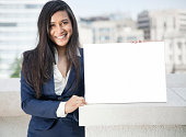 Portrait of a young Indian businesswoman holding Moodboard sign