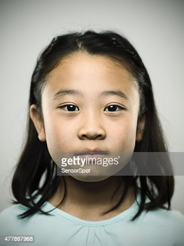 Portrait of a young japanese girl looking at camera.