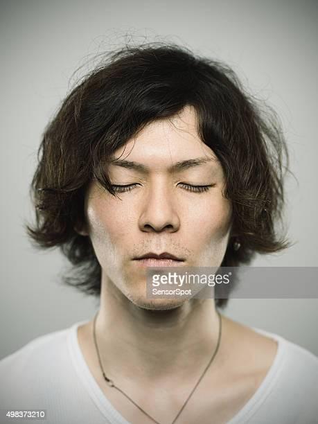 Porträt eines jungen japanischen Mann mit Augen geschlossen