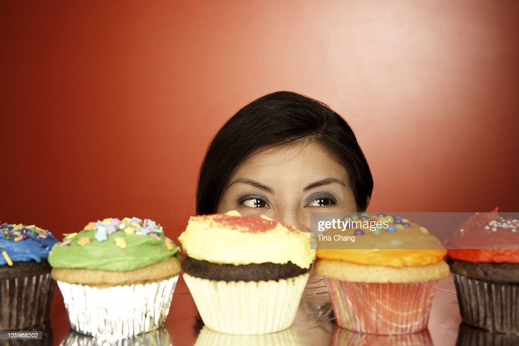 Portrait of a young lady with a line up of colorful cupcakes : Stock Photo
