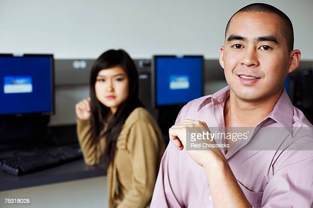 Portrait of a young man and a young woman sitting in front of computers and grinning