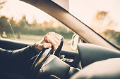 Man driving a car, close up on a steering wheel