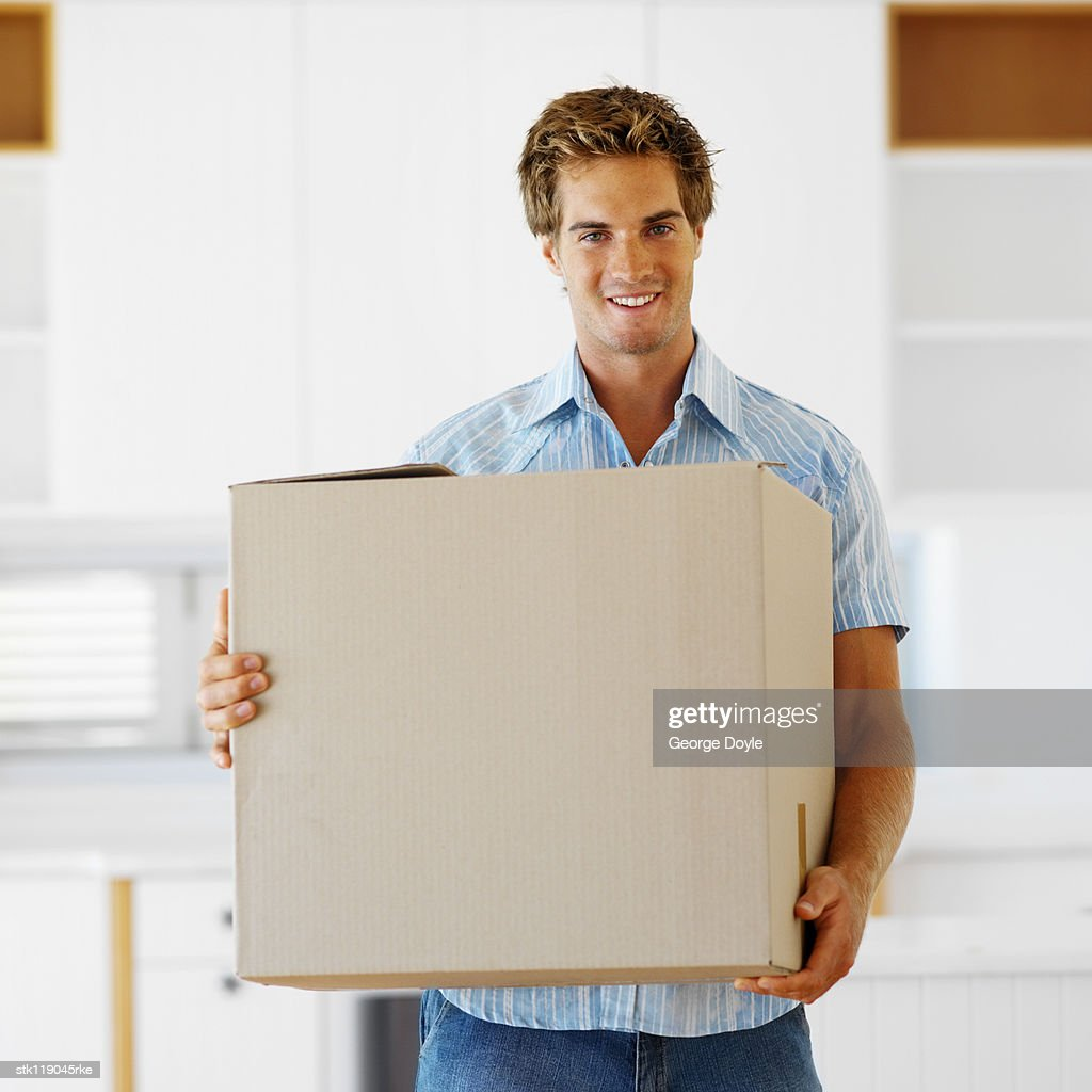 portrait of a young man carrying a cardboard box : Stock Photo