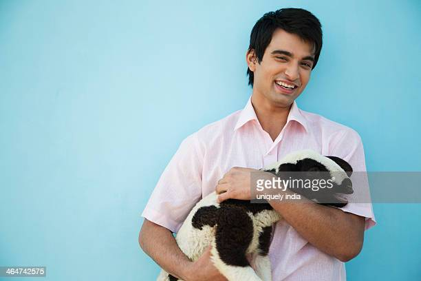 Portrait of a young man carrying a lamb and smiling