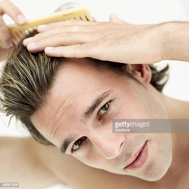 portrait of a young man combing his hair
