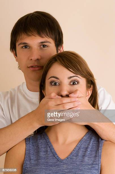 Portrait of a young man covering young woman's mouth from behind