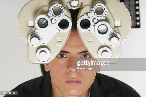 Portrait of a young man having sight test : Stock Photo