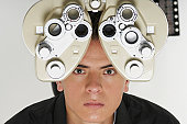 Portrait of a young man having sight test
