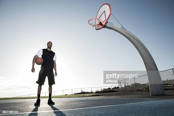 Portrait of a young man holding a basketball in a park, Los Angeles, California, USA