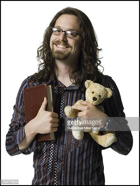 Portrait of a young man holding a book and a teddy bear