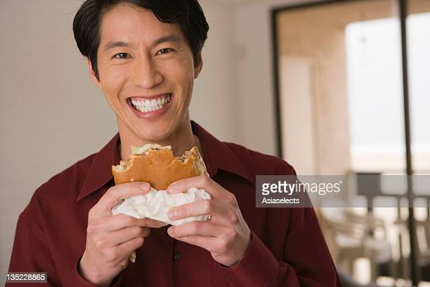Portrait of a young man holding a burger and smiling