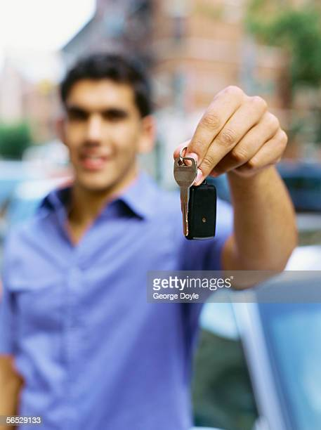 portrait of a young man holding a car key