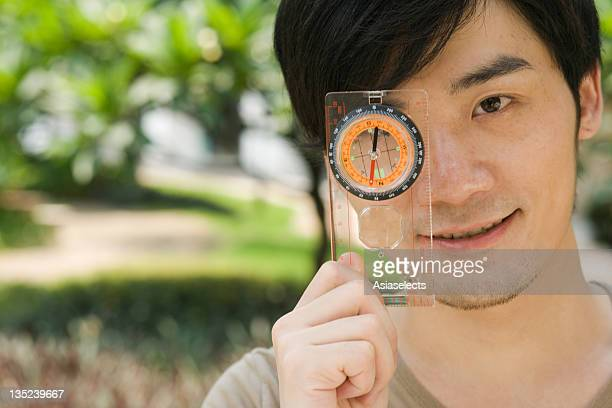 Portrait of a young man holding a compass near his eye and smiling